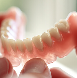 person holding a partial denture