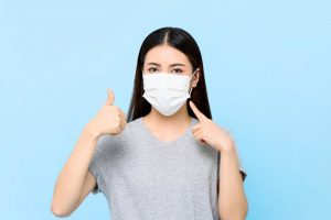 young woman wearing face mask to dental visit