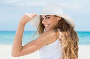 woman on the beach showing off her smile with dental implants